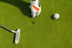 Marking golf ball position at the green. Focus on marker. Royalty Free Stock Image
