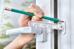 Marking holes for fixing tilt restrictor PVC window. Stock Photos