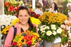 Marknadsför färgrika blommor för gladlynt blomsterhandlarekvinnavisning arkivbild
