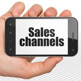 Marknadsföringsbegrepp: Räcka hållande Smartphone med försäljningskanaler på skärm Arkivbilder