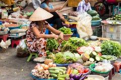 Marknadskvinna som säljer grönsaker Arkivbild