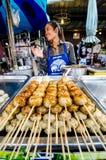 Marknadskvinna som säljer grillade köttbullar. Fotografering för Bildbyråer