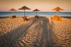 Markotny pokojowy plaży i morza widok z sunshades przy zmierzchu chillout koloru rozszczepionym tonowaniem obrazy stock