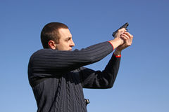 Marksman. Man in blue sweater with gun Royalty Free Stock Images