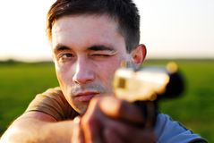 The marksman from a pistol. The man shoots from a pistol on a green field Royalty Free Stock Images