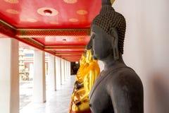 Markstein, Abschluss herauf schöne schwarze Buddha-Statue, stehende Buddha-Statue, goldener Statue Tempel Wat Pho in Asien Bankok Stockfotografie