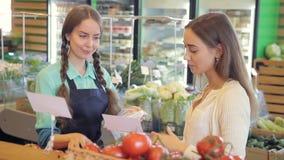 Marktangestellter hilft, Tomaten für Frauenkunden zu verpacken In der Lebensmittelabteilung stock video footage