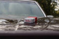 Marlboro som är röd på bils huv royaltyfri bild