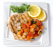 Marlin steak meal from above. Marlin steak grilled and served with a tomato onion salsa viewed from above stock photos
