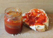 Marmalade for breakfast. Jar of marmalade and a piece of bread Royalty Free Stock Photography