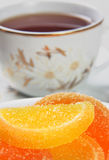 Marmalade close-up and a cup of tea. Royalty Free Stock Photo