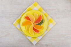 Marmalade in form of citrus fruits in saucer on napkin Royalty Free Stock Images