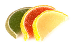 Marmalade in form of slices of citrus fruits on white Royalty Free Stock Photos