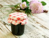 Marmalade in glass and flowers on wooden Stock Image
