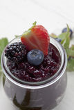 Marmalade in jar fresh strawberry blueberry blackberry on top royalty free stock photography