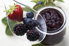 Marmalade in jar strawberry blueberries blackberries on plastic spoon close up stock image