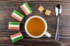 Marmalade, sugar cubes, tea in cup and teaspoon on table. Marmalade, sugar cubes, tea in cup and teaspoon on wooden table. Top view Royalty Free Stock Photography