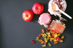 Marmalade in a vase on the table. Sweets in a bowl on a black ba. Marmalade in a vase on table. Sweets in a bowl on a black background. Multicolored jelly sweets Stock Image