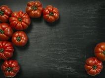 Marmande tomatoes on slate background. Photo of a table top with Marmande tomatoes over a slate background stock photo
