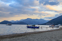 Marmaris beach with fishing boats on mountains background. During sunset Stock Photo