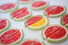 Marmelad i form av skivor av vattenmelon- och limefruktlögner på en vit yttersida folkmassan ut plattforer arkivbilder