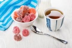 Marmellata d'arance rossa in ciotola, zucchero, tè, tovagliolo blu e cucchiaino Fotografie Stock
