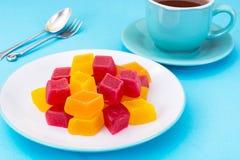Marmellata d'arance sul piatto e tè in tazza, fondo blu Immagine Stock Libera da Diritti