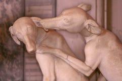 Marmeren beeldhouwwerk waar twee honden op de achtergrond van een marmeren muur kussen stock foto