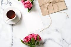 Marmeren bureau met roze bloemen, prentbriefkaar, kraftpapier-envelop, streng, katoenen tak stock fotografie