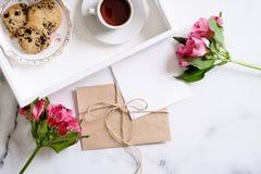 Marmeren bureau met roze bloemen, prentbriefkaar, kraftpapier-envelop, streng, katoenen tak, uitnodigingskaart met exemplaarruimt royalty-vrije stock foto