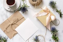 Marmeren bureau met roze bloemen, prentbriefkaar, kraftpapier-envelop, streng, katoenen tak, uitnodigingskaart met exemplaarruimt stock foto