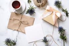 Marmeren bureau met roze bloemen, prentbriefkaar, kraftpapier-envelop, streng, katoenen tak, uitnodigingskaart met exemplaarruimt royalty-vrije stock afbeelding
