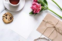 Marmeren bureau met roze bloemen, prentbriefkaar, kraftpapier-envelop, streng, katoenen tak, uitnodigingskaart met exemplaarruimt stock afbeeldingen