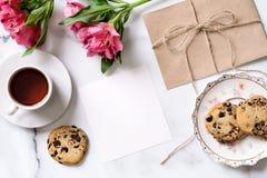 Marmeren bureau met roze bloemen, prentbriefkaar, kraftpapier-envelop, streng, katoenen tak, uitnodigingskaart met exemplaarruimt royalty-vrije stock foto's