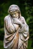 Marmeren parkbeeldhouwwerk van een oude mens die en in spreien wordt verpakt bevriezen die het koude seizoen van het jaar verpers Stock Afbeelding