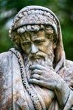 Marmeren parkbeeldhouwwerk van een oude mens die en in spreien wordt verpakt bevriezen die het koude seizoen van het jaar verpers Stock Foto