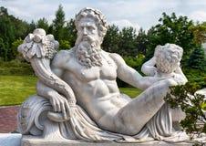 Marmeren standbeeld van Griekse Olympische god met hoorn des overvloeds in zijn handen stock afbeeldingen