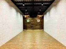 Marmeren tegelgang aan mannelijke en vrouwelijke badkamerss met witte bric Royalty-vrije Stock Foto