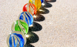 Marmi di vetro variopinti sulla sabbia Fotografia Stock Libera da Diritti