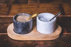 Marmorera exponeringsglas med kryddor, och smaktillsatser står på en träställning Royaltyfri Bild