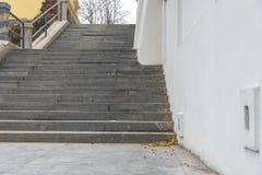 Marmorera skada och smutsig trappa med den vita husväggen i staden arkivfoto