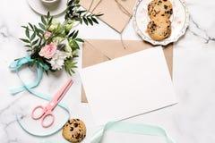 Marmorera skrivbordet med buketten av blommor, rosa sax, vykortet, det kraft kuvertet, bomullsfilialen, havrekakor, inbjudankort  royaltyfri fotografi