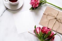 Marmorera skrivbordet med buketten av blommor, rosa sax, vykortet, det kraft kuvertet, bomullsfilialen, havrekakor, inbjudankort  arkivbilder