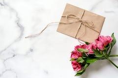 Marmorskrivbordet med rosa färger blommar, vykortet, det kraft kuvertet, tvinnar, bomullsfilialen arkivbild