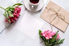 Marmorskrivbordet med rosa färger blommar, vykortet, det kraft kuvertet, tvinnar, bomullsfilialen arkivfoton