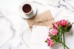 Marmorskrivbordet med rosa färger blommar, vykortet, det kraft kuvertet, tvinnar, bomullsfilialen arkivbilder