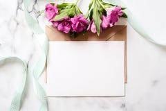 Marmorskrivbordet med rosa färger blommar, vykortet, det kraft kuvertet, tvinnar, bomullsfilialen, inbjudankort med kopieringsutr arkivbilder