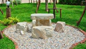 Marmorstuhl auf Kieseln im Garten haben Grashintergrund Stockfotos