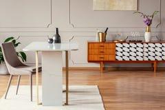Marmortabelle nahe bei einem Stuhl in einem eklektischen Esszimmer mit einem Retro- Kabinett stockfotos