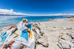 Marnyi stone with sutra streamers on the lakeside of Namtso Royalty Free Stock Images